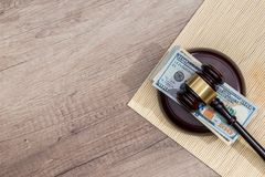 Us money with wooden judges hammer on table. Top view stock image