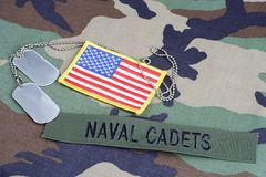 US NAVAL CADETS branch tape, flag patch and dog tags on woodland camouflage uniform. Background Stock Photography