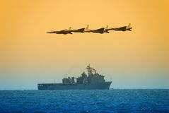 US Navy attack. Military jet fighters flying over military carrier at sunrise royalty free stock image