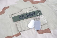 US NAVY branch tape with dog tags with dog tags on desert camouflage uniform. Background Royalty Free Stock Images