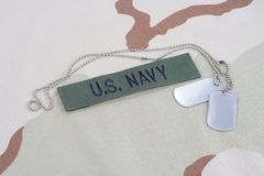 US NAVY branch tape with dog tags with dog tags on desert camouflage uniform. Background Royalty Free Stock Image