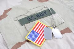 US NAVY branch tape with dog tags and flag patch on desert camouflage uniform. Background Stock Images