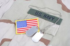 US NAVY branch tape with dog tags and flag patch on desert camouflage uniform. Background Royalty Free Stock Images