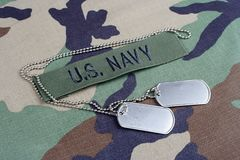 US NAVY branch tape and dog tags on woodland camouflage uniform. Background Royalty Free Stock Photography