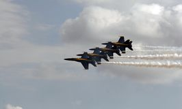 US Navy's Blue Angels. Four US Navy Blue Angels flying in a tight formation at an airshow. Smoke is on stock photos