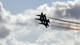 US Navy's Blue Angels. Four US Navy Blue Angels flying in a tight formation at an airshow. Smoke is on stock photo