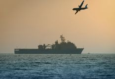 US Navy warship. Airplane flying over warship in early morning stock image