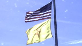 US and New Mexico flags in high wind stock video footage