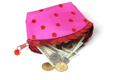 US notes and coins spilling out from pink purse Royalty Free Stock Image