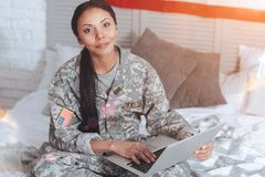 Joyful positive woman holding a laptop. US officer. Joyful positive smart woman sitting on the bed and holding a laptop while wearing a military uniform royalty free stock photo