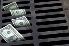 US One Dollar bills washed down the drain. US Dollar bills down the street drain Royalty Free Stock Photography