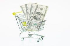 US one hundred dollar bills in shopping cart. American one hundred dollar banknotes in shopping cart over white background Stock Image