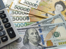US one hundred dollar and Korean banknotes with calculator Royalty Free Stock Images