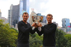 US Open 2014 campeões Bob e Mike Bryan dos dobros dos homens que levantam com o troféu no Central Park fotografia de stock royalty free