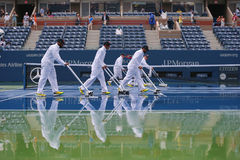 US Open cleaning crew drying tennis court after rain delay at Arthur Ashe Stadium Stock Images