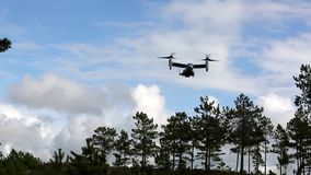 US Osprey Fligh Over Forest. A US Osprey aircraft fly at a cloudy day over some trees stock video footage