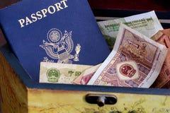 US-Paß mit chinesischem Bargeld im hölzernen Kasten Stockbild