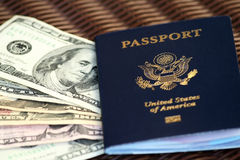 US Passport and dollar bills. American passport with various denominations of US dollar bills