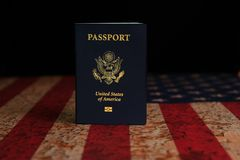 US Passport standing on rustic American Flag with black background stock photos