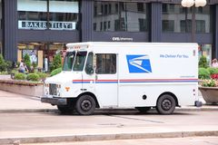 US Postal Service. CHICAGO - JUNE 26: People walk past US Postal Service truck on June 26, 2013 in Chicago. USPS is the operator of the largest civilian vehicle Royalty Free Stock Photo