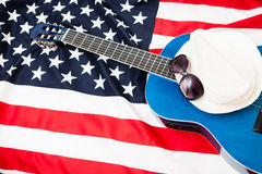US pro musicians. Guitar lies on the flag of Britain. Glasses on Stock Photos