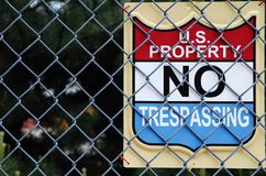 US Property No Trespassing. Sign attached to a chain link fence Stock Photos