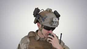 US ranger in uniform talking on radio on gradient background.