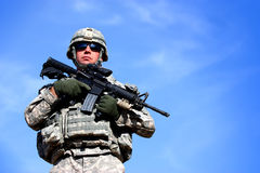 A US soldier. Guarding while holding his weapon outside isolated on a blue sky background