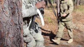 A US Soldier Aim In Forest And Walk Away. A US soldier aim a target at a training. After that he walks with his trainer away stock video footage