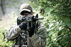 US soldier on battle field. US special forces  soldier aiming for precise shot, hiding behind bushes Royalty Free Stock Image