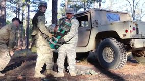 US Soldier Carry Training Injured Soldier Out OF Car. US soldiers carry a injuerde soldier out of a military car at a training stock video