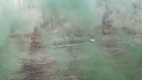 US Soldier Checks Injured Soldier On Litter At Training. A US soldier checks a injured soldier who lie on a litter. In front of them flows green smoke stock video