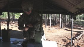 US Soldier Installs Radio. A US soldier installs a microphone at a radio. The soldier stand in front of a table in a tent stock video footage