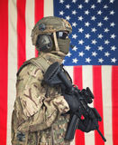 US soldier with machine gun in hands and American flag on background Royalty Free Stock Photo