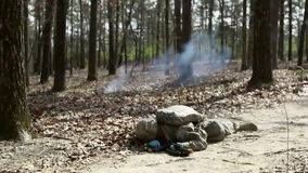 US Soldier Military Training Simulates Grenade Impact. A US soldier runs in a forest at a military training. He slaps down to the ground as a simulation with a stock video footage