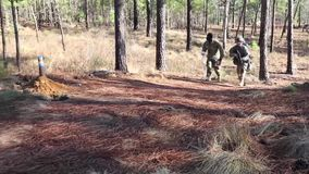 US Soldier Runs Trainer Through Forest. A US soldier runs at a training with a trainer through a forest stock video