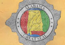 US state Alabama seal flag in big concrete cracked hole royalty free stock photography