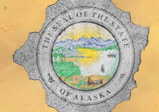 US state Alaska seal flag painted on concrete hole and cracked wall stock image