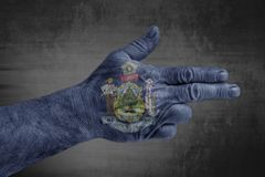 US State Maine flag painted on male hand like a gun royalty free stock photo
