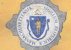 US state Massachusetts seal flag painted on concrete hole and cracked wall. Facade structure royalty free stock images