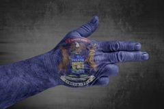 US State Michigan flag painted on male hand like a gun royalty free stock photography