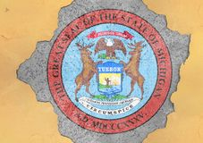 US state Michigan seal flag in big concrete cracked hole and broken wall. US state Michigan seal flag in big concrete cracked hole and broken material facade royalty free stock photography