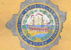 US state New Hampshire seal flag painted on concrete hole. And cracked wall facade structure stock photo