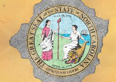 US state North Carolina seal flag painted on concrete hole. And cracked wall facade structure stock image