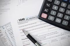 US-Steuerformular 1040 mit Stift und Taschenrechner Stockfotos