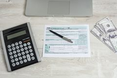 US tax form next to computer laptop, dollar bills, calculator and tax form 1040. tax form us business income office hand stock photography