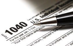 US 1040 tax form with pen. And coins Stock Photos