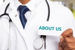 About us text on card held by physician. Blue about us text on white business card held by male indian physician or doctor close-up stock photography