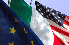 Us and Them. Europe, Italy and United states flags in the wind Royalty Free Stock Photo