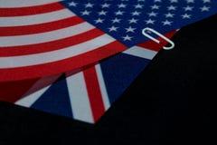 US- und Großbritannien-Flaggen schlossen sich bij eine Papierklammer an Lizenzfreie Stockbilder